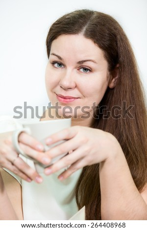 Facial portrait of young woman with tea mug in hands, grey background - stock photo