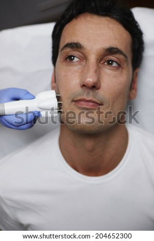 Facial rejuvenation procedure, handsome man at the reception at the clinic, middle age man undergoing rejuvenation skin treatment with a laser - stock photo