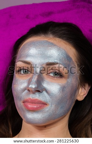 Facial Skin Care. Drawing a silver mask on the face of a beautiful girl. Anti-aging facial mask. - stock photo
