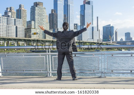 Facing dramatic high buildings of New York City, a middle age businessman is raising both arms, a symbol of success. / Welcome Home - stock photo