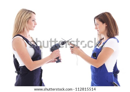 Facing off to a duel Humorous image of two DIY housewives facing off to a duel as they stand face to face with crossed power tools - stock photo