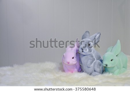 Facing view of three different colored easter bunnies on a white fur surface, in front of a light grey background