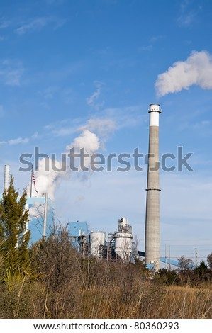 Factory and Smoke Stack Releasing Pollution into the Sky - stock photo