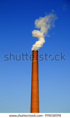 Factory chimney A factory chimney with rising smoke under a blue sky - stock photo