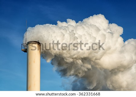 factory chimney and smokestack on blue sky background - stock photo