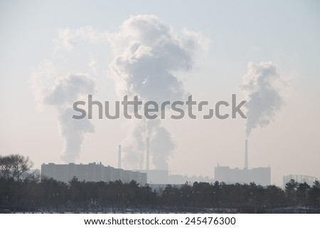 Factory chimney in winter - stock photo