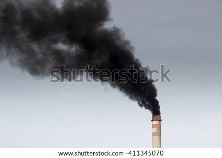 Factory chimney smoking, heavy black smoke on the sky. - stock photo