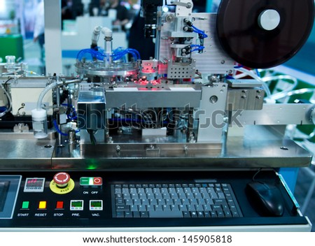 Factory control room with machine controled by computer. - stock photo