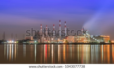 Factory in night time beside big river.