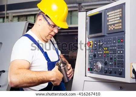 Factory man worker measuring steel detail with digital Vernier Caliper at workshop - stock photo