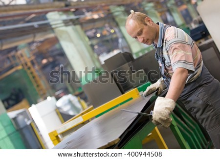 Factory man worker removing metal burrs from metal parts' surface with deburing tool - stock photo