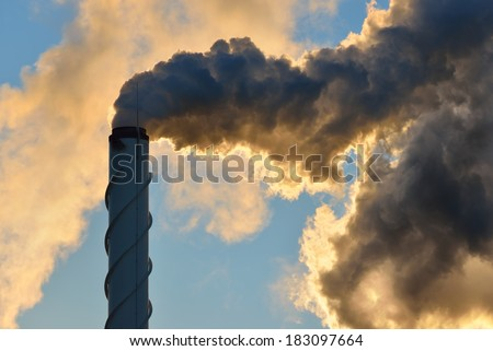 Factory pipe close-up with a lot of smoke against blue sky - stock photo
