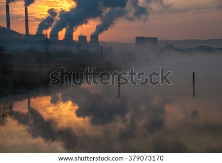 Factory pipe polluting air, smoke from chimneys reflect in river water against sunset, environmental problems, ecology theme - stock photo