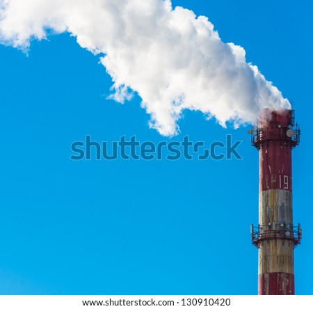 Factory pipe produces smoke in the sky - stock photo