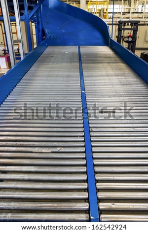 Factory roller conveyor system for transporting crates - stock photo