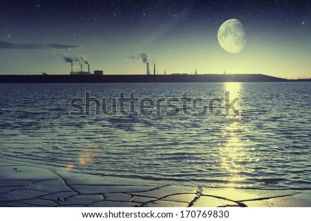 factory smoke from a pipe on a background of lake at sunset. Elements of this image furnished by NASA