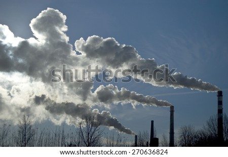 Factory tubes and white smoke against blue sky. Industrial scene.