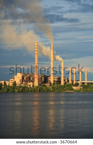 factory with chimney-stalks on a river bank