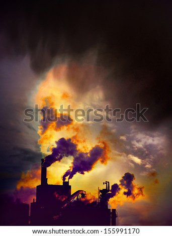 Factory with chimneys emitting smoke on blue sky - stock photo