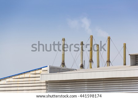 factory with smokestacks on roof against blue sky  - stock photo