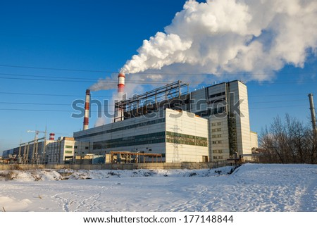 factory with smoking chimneys against the blue sky