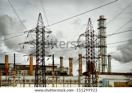factory with smoking pipes and electric towers