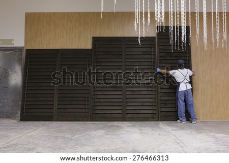 Factory worker applying stain to shutter panels.