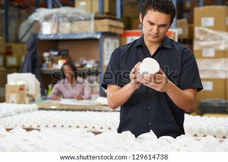 Factory Worker Checking Goods On Production Line - stock photo