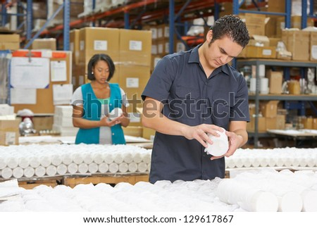 Factory Worker Checking Goods On Production Line