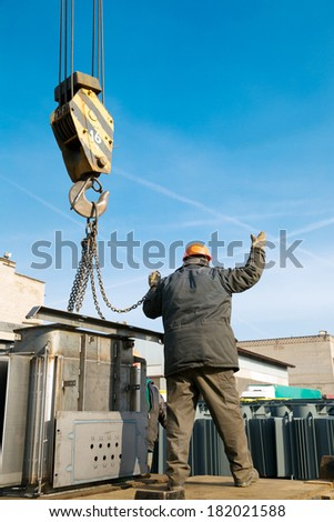 Factory worker gesturing during loading and unloading cargo works with crane at industrial site - stock photo