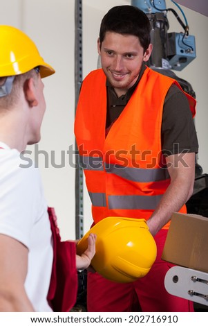 Factory worker giving his collaborator hardhat, vertical - stock photo