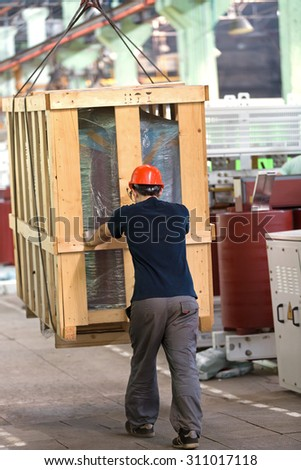 Factory worker in helmet transporting cargo box with workshop rail mounted gantry crane - stock photo