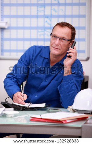 Factory worker ordering more stock - stock photo
