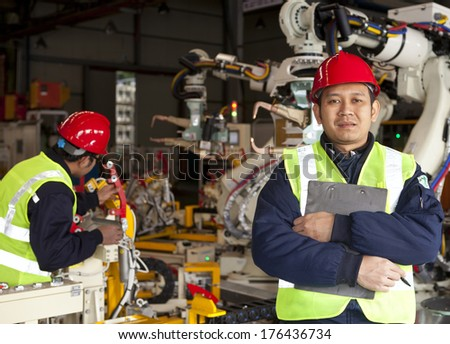 Factory worker standing with partner on the background