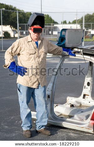 Factory worker taking a smoke break, leaning against a disassembled automobile. - stock photo