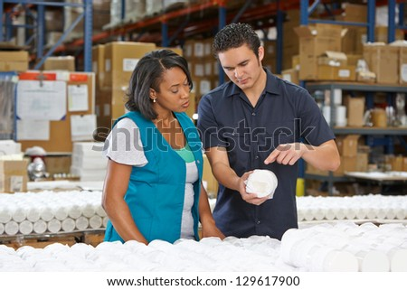 Factory Worker Training Colleague On Production Line - stock photo