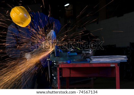Factory worker using electric grinder - a series of METAL INDUSTRY images. - stock photo