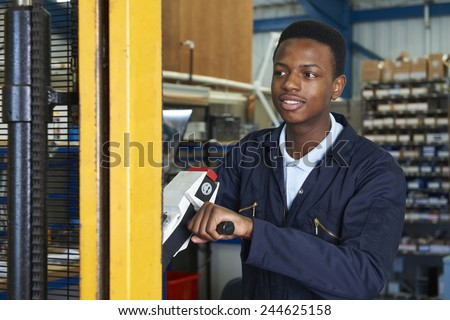 Factory Worker Using Powered Fork Lift To Load Goods