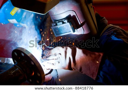 factory worker welding metal and sparks spreading - stock photo