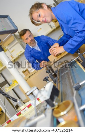 Factory workers boxing finished product off of conveyor - stock photo
