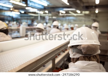 Factory workers grouped at working facility with safety gear and machinery - stock photo