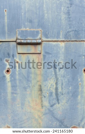 Faded Blue steel metal with water erosion drip, yellow green rust, hole punctures, and hinge - stock photo