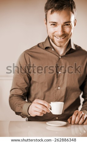 Faded effect image of a smiling happy bearded young man in a brown shirt enjoying a cup of coffee sitting at a table looking at the camera with a beaming grin - stock photo