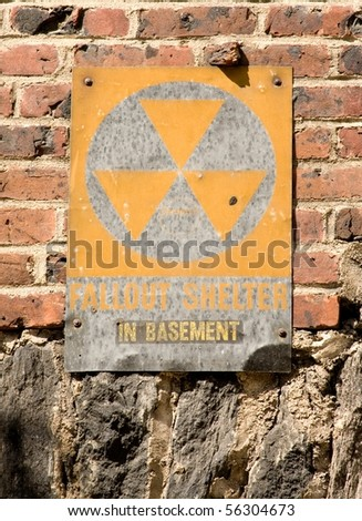 Faded fallout shelter sign on brick - stock photo