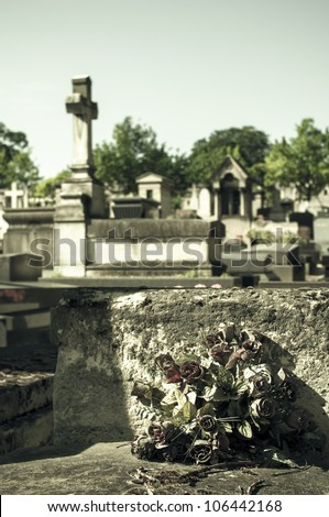 Faded flowers on an old grave - stock photo
