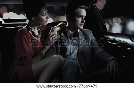 Faded image of beautiful couple sitting in a limousine