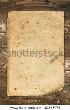 Faded old paper sheet on a wooden background