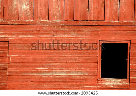 faded red barn siding with black window square hole on right lower corner - stock photo