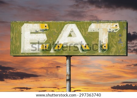 Faded vintage eat sign with sunset sky. - stock photo