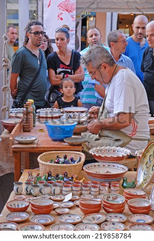 FAENZA, ITALY- SEPTEMBER 7, 2014: artist painting a plate at the ceramic Sunday market. The market is very popular in the city and attracts thousands of people. - stock photo